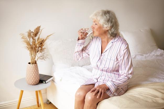 朝の儀式、レジャー、休息、就寝時のコンセプト。居心地の良いインテリアのベッドに座って、マグカップを持って、消化器系を機能させるために水を飲む白髪の魅力的な女性年金受給者