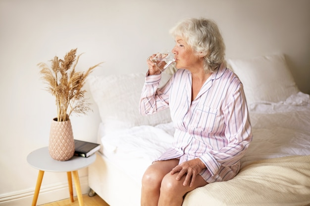 Morning rituals, lesiure, rest and bedtime concept. attractive female pensioner with gray hair sitting on bed in cozy interior, holding mug, drinking water to make her digestive system work