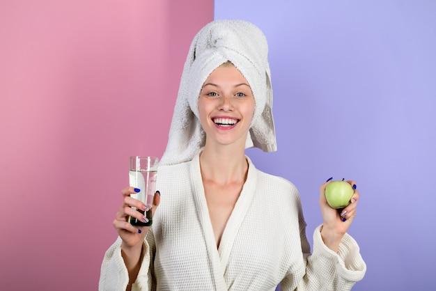 アップルと水の健康健康的なライフスタイルの女の子のガラスで睡眠の女性を目覚めさせる朝のルーチン