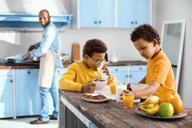 毎朝の日課。魅力的な男の子がテーブルに座って、父親が料理をしながら朝食をとる