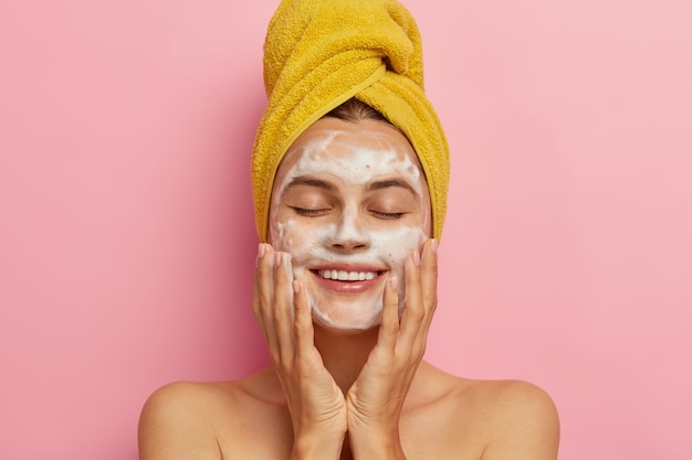Routine mattutina e concetto di tempo rilassante. la giovane donna soddisfatta lava il viso, pulisce la pelle con il sapone, indossa un asciugamano giallo sulla testa, tiene gli occhi chiusi dal piacere