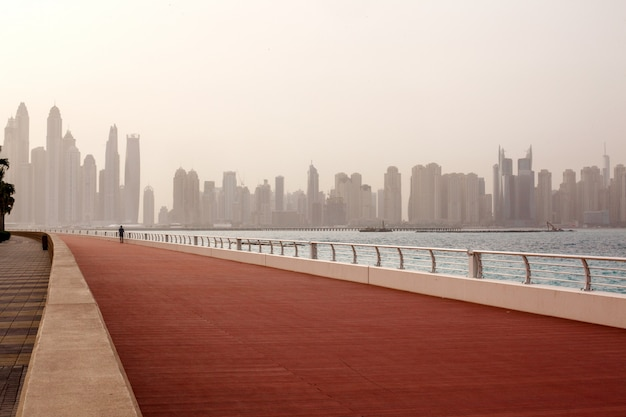 Morning run, a man runs along the road with a beautiful view of dubai. uae