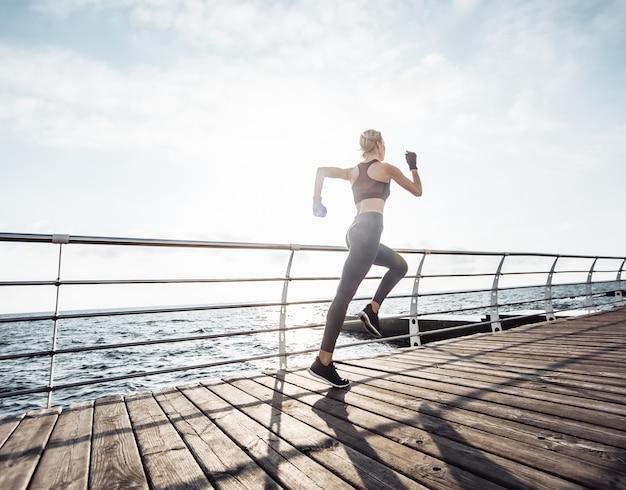 Утренняя пробежка молодая спортивная женщина в спортивной одежде бежит по пляжу на рассвете
