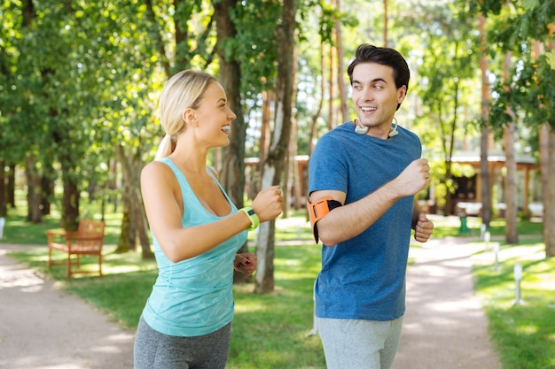 Morning runners. happy nice couple looking at each other while running together in the morning
