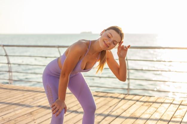 朝のランニングトレーニングのコンセプトです。日の出ビーチでスポーツウェアの若い疲れたフィット女性。