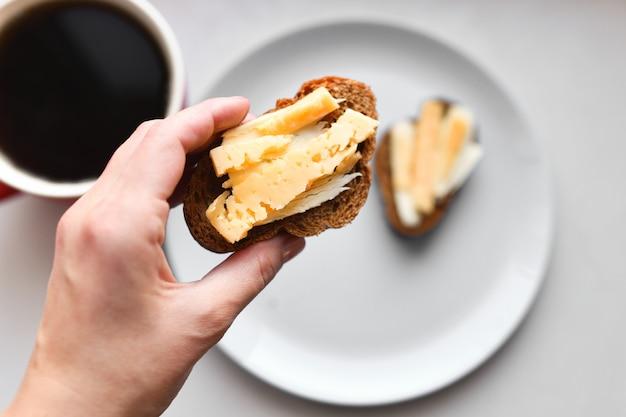 Утренние бутерброды с кофе. хлеб с сыром и маслом.