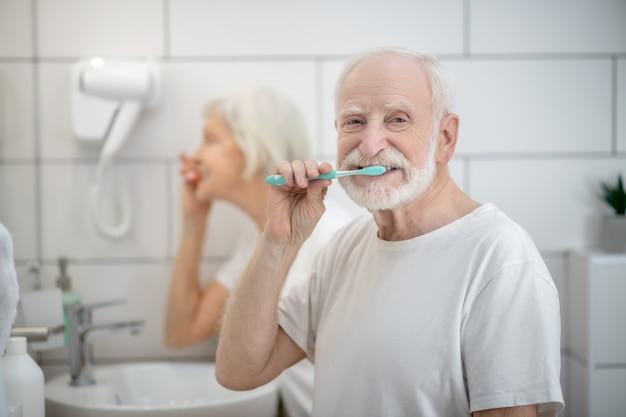 朝。老夫婦がバスルームで一緒に歯を磨く