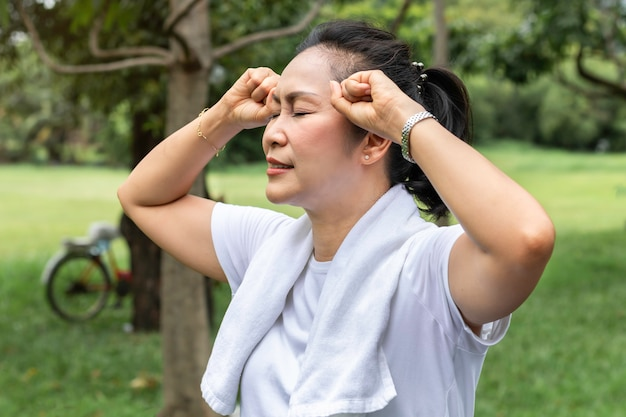 In the morning.senior woman asian headache during exercise at the park.