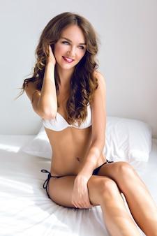 Утренний чувственный сексуальный портрет потрясающей молодой женщины, только что проснувшейся в белой спальне, наслаждающейся своим утренним временем, одетой в милое повседневное белье, стильный макияж, мягкие пастельные тона.