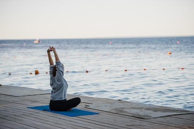 桟橋でストレッチヨガの練習をしている蓮華座の女の子のモーニングショット