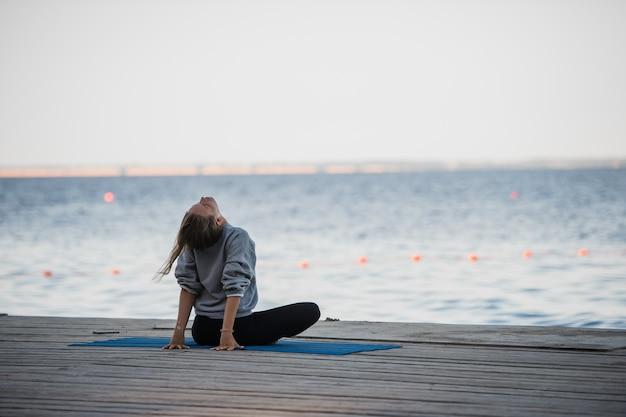 桟橋でストレッチヨガの練習をしている蓮華座の女の子の朝のショット