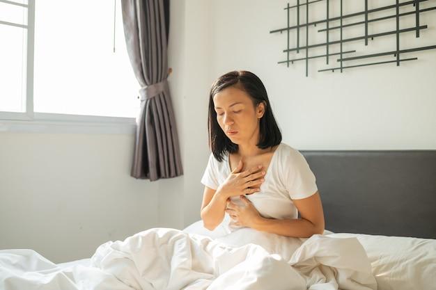 つわり。ベッドに座って、妊娠中に吐き気を感じて口を覆っている若い妊婦、朝、ベッドで目を覚ますときに酸逆流症に苦しんでいる白いパジャマの女性。