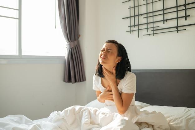 입덧. 임신 중 메스꺼움을 느끼는 입을 덮고 침대에 앉아 젊은 임산부, 아침에 침대에서 일어나는 동안 산성 역류로 고통받는 흰 잠옷을 입은 여성.