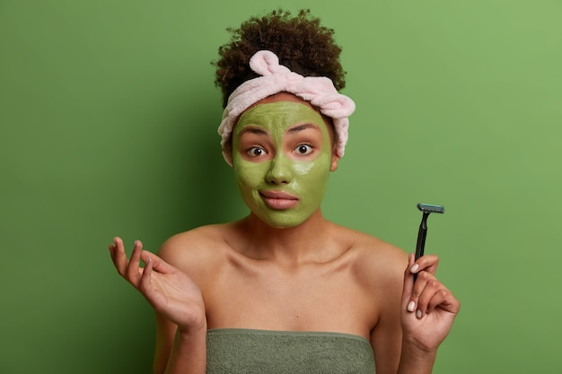 Утренний уход за кожей. ничего не подозревающая женщина в нерешительности пожимает плечами, наносит увлажняющую маску на лицо, держит бритву для бритья, завернувшись в банное полотенце, позирует на фоне ярко-зеленой стены.