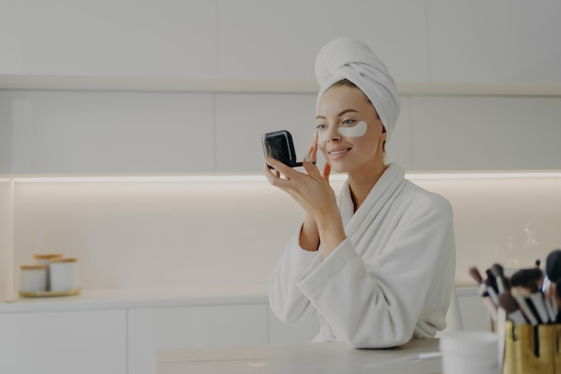 Morning skin care routine. young beautiful woman in bathrobe and hair wrapped in towel applying cosmetic patches under eyes from dark circles and looking in compact mirror while standing in kitchen