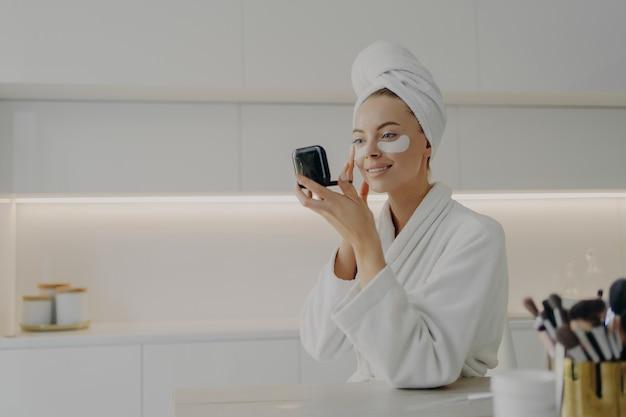 Утренний уход за кожей. молодая красивая женщина в халате и волосах, завернутых в полотенце, наносит косметические патчи под глаза от темных кругов и смотрит в компактное зеркало, стоя на кухне