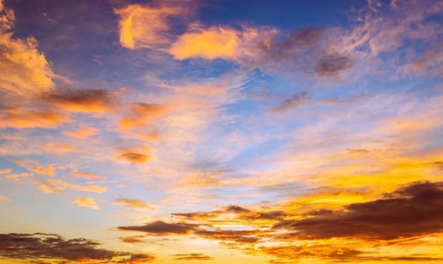 カラフルなオレンジ色の日の出とふわふわの雲と朝空の背景
