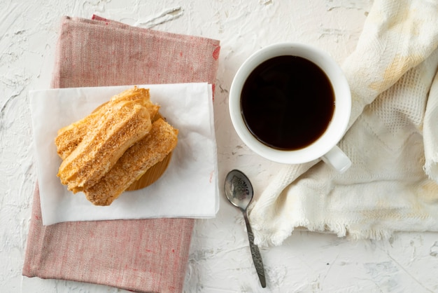 Morning snack with coffee and creamy eclair on a table with white tablecloth, business breakfasts