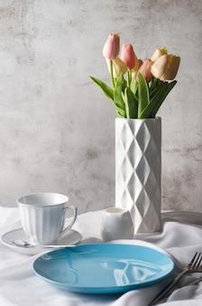 朝の春のテーブルセッティングの装飾。空のセラミックプレート、カップ、きれいな白いテーブルクロスの背景に花瓶の新鮮なチューリップ。夕食または朝食のコンセプト、