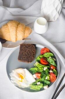 朝の春のテーブルセッティングの装飾。プレートのサラダ、卵、一杯のコーヒーとクロワッサン、