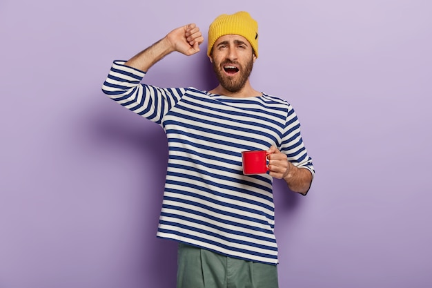 Утро начинается с кофе. сонный мужчина потягивается после пробуждения, пьет горячий напиток, чтобы освежиться, держит красную чашку, говорит