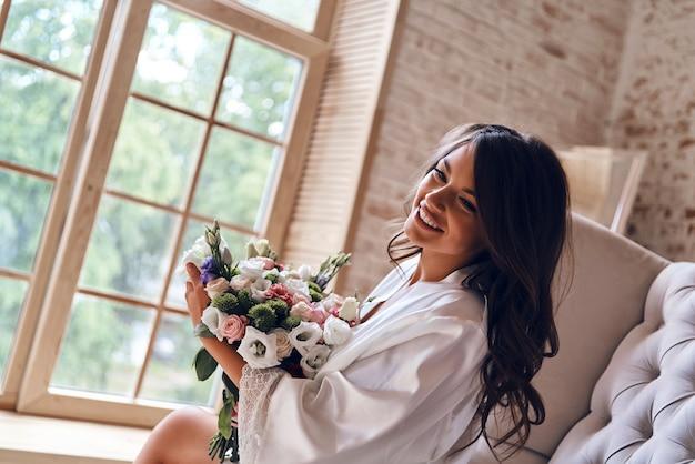 朝は花から始まります。花束を持ってソファに座って笑っているシルクのバスローブで魅力的な若い女性