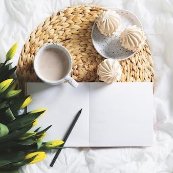 一杯のコーヒー、チューリップ、スケッチブックのある朝の静物。上面図、正方形