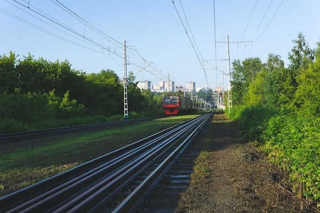Morning suburban landscape with electric commuter train moving from the city on the horizon