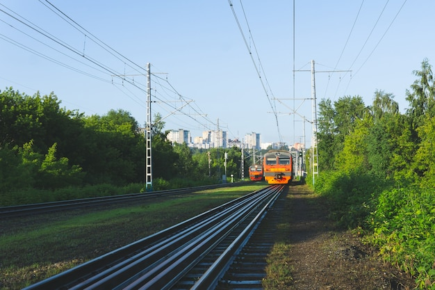 Morning suburban landscape with two electric commuter trains and city on a hill in the distance