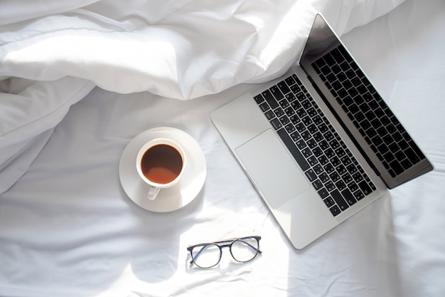 Morning sun shines on the laptop and coffee on the bed, the white sheet in the top view