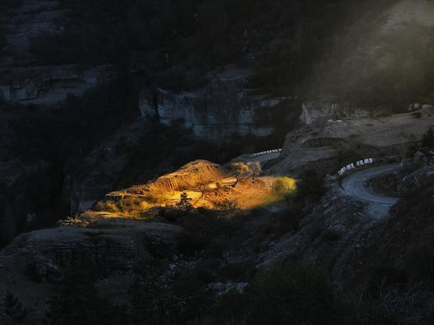 朝日が山を照らし、曲がりくねった道が山から降りてきます。