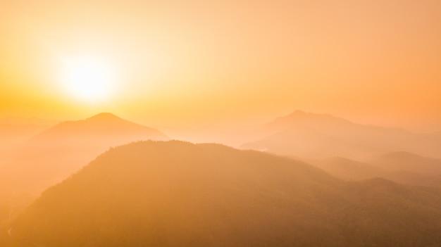 Утренний восход солнца над горами с тусклым туманом