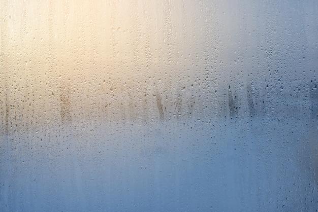 ガラス上の雨滴を通して朝日の出