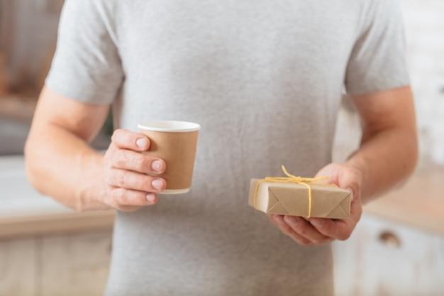 Утренний сюрприз. обрезанный снимок человека, держащего чашку кофе и обернутый подарок ручной работы.