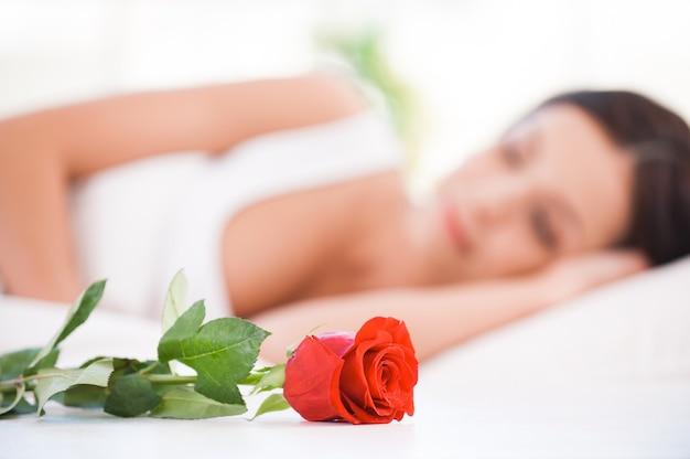 아침 놀람. 빨간 침대에 누워 있는 아름 다운 젊은 여자의 측면 보기