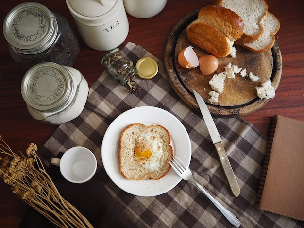 Morning table breakfast of bread and egg with a cup of tea on brown checkered tablecloth
