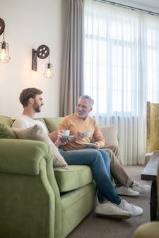 Morning talks. two men sitting on the sofa and having tea