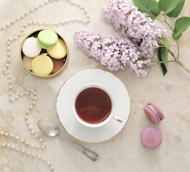 Morning tea with cookies, macarons, and a branch of lilac