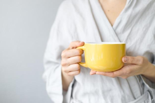 レモン白人女性との朝のお茶は紅茶黄色いカップにレモンを入れます
