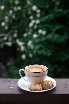 Morning tea with lemon and cookies on a cozy outdoor terrace overlooking a blooming garden.