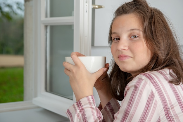 Morning, teenage girl is drinking coffee in a bowl