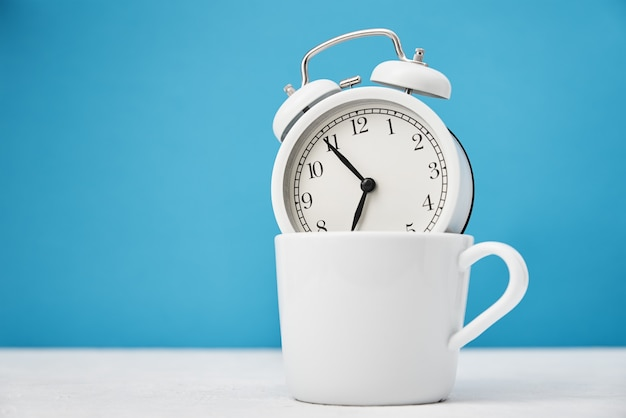 Morning time concept. white retro alarm clock in cup on blue