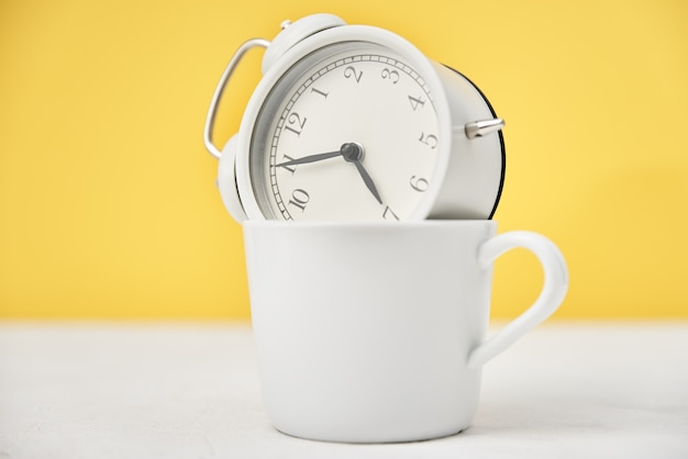 Morning time concept. white retro alarm clock in cup on yellow background
