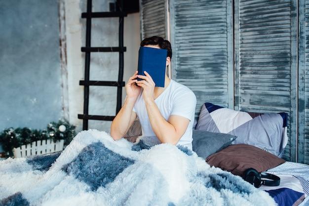 Утреннее время студента. красивый парень читает книгу дома