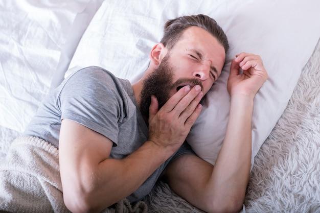 朝。起きる時間。目を閉じて大きくあくびをしているベッドに横たわっている男。寝たい。
