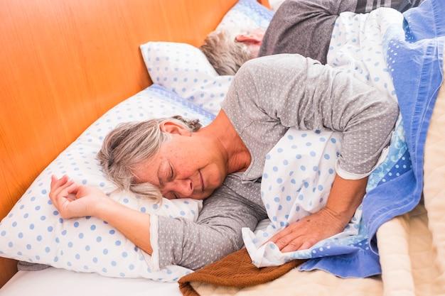 朝の時間は、ベッドで自宅で大人のシニアoupleのために目を覚ます。窓からの光の中で一緒に寝る、デイライフのコンセプト。疲れた高齢の白人の人々のための素敵な休息。白い枕