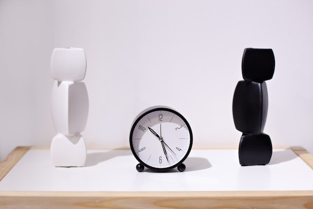 Morning time wall, alarm clock near bed at home. classic alarm clock and two vases in black and white. front view desk with round black clock with an ceramic vase on white wall. minimalism