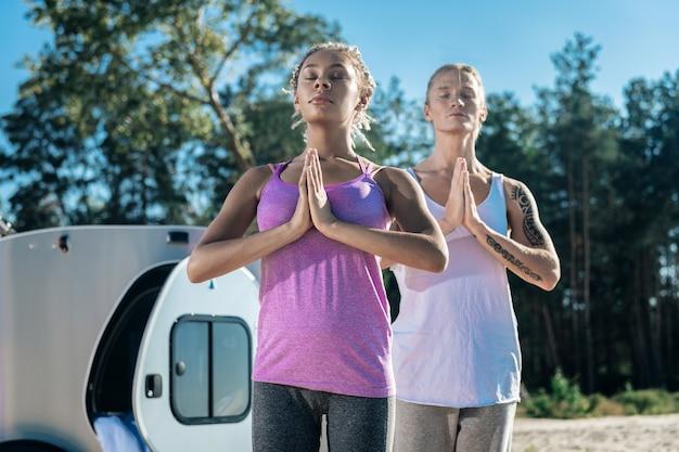 一緒に朝。一緒に朝瞑想しながらゆっくり呼吸するコンパクトトレーラーに住んでいるカップル