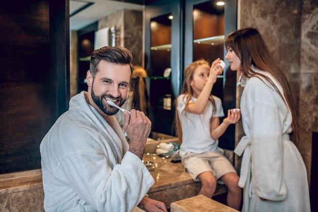 一緒に朝。一緒に歯を磨くバスローブのかわいい家族