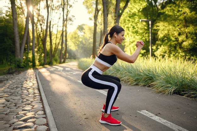 여름 공원에서 아침 훈련, 스트레칭 운동을하는 여자. 여성 러너는 화창한 날에 스포츠에 간다